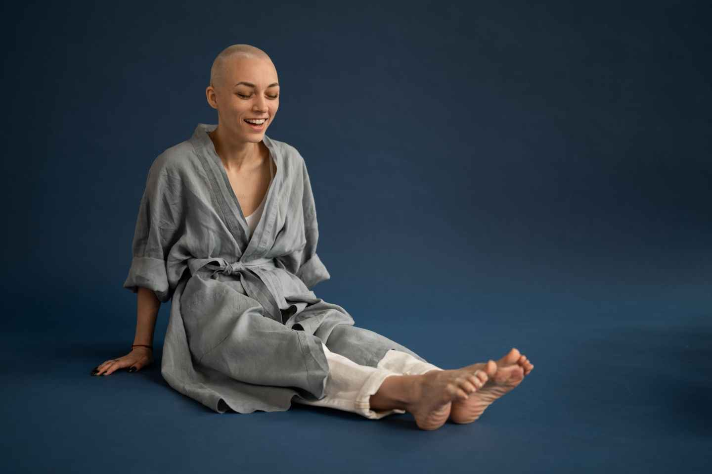 content bald woman sitting on floor in dark studio