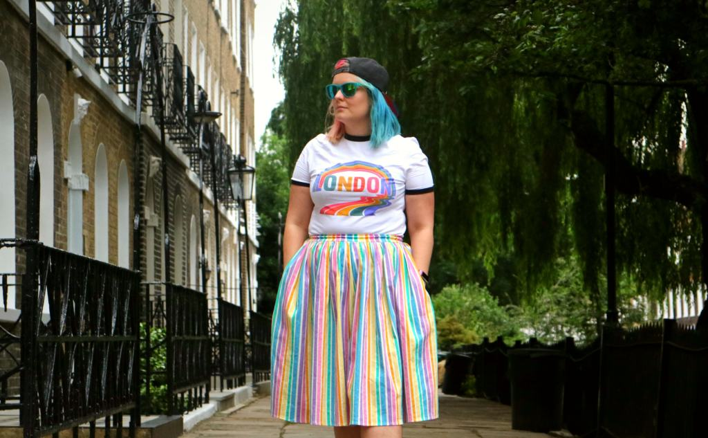 girl standing in a street in a Pride in London t shirt and pastel rainbow stripped skirt pride fashion