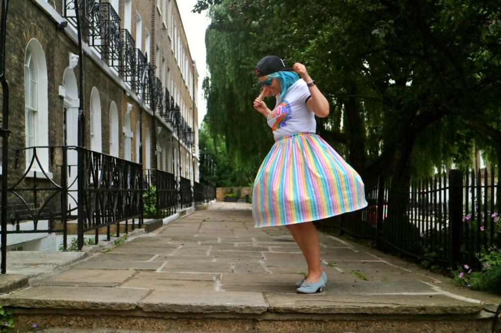 girl in a colourful skirt spinning in the street pride fashion
