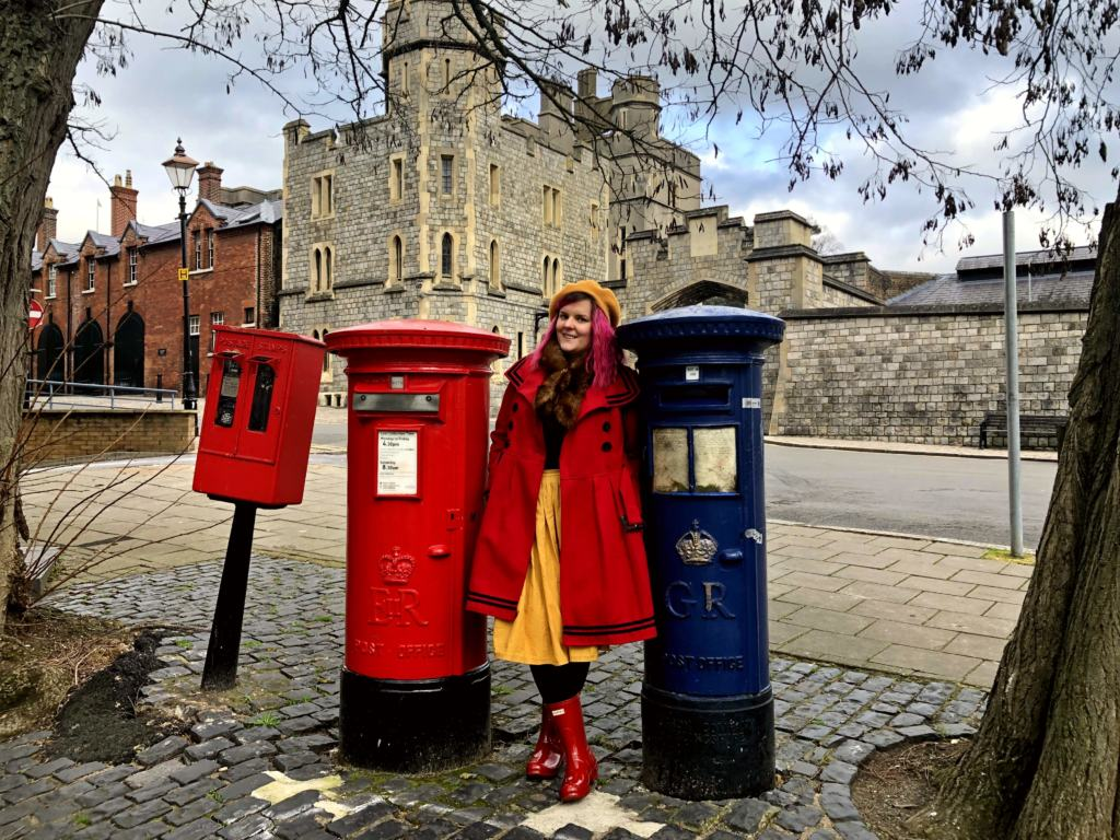 woman in red coat next to the worlds first airmail box and regular postbox in Windsor