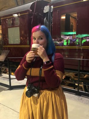 woman drinking butterbeer in front of the Hogwarts express in the Warner Bros. Studio