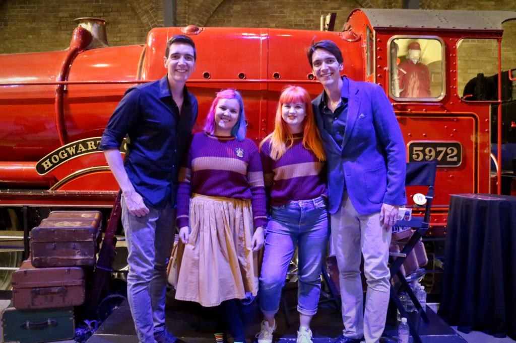 Two women in Gryffindor uniforms meeting the Weasley Twins at the Warner Bros. Studio tour in front of the Hogwarts Express