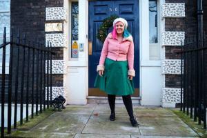 Kariss laughing in green midi dress and pink coat