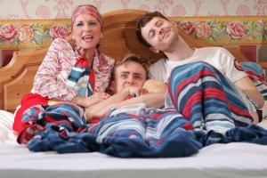 man in bed looking embarrassed with man and another next to him in The Morning After