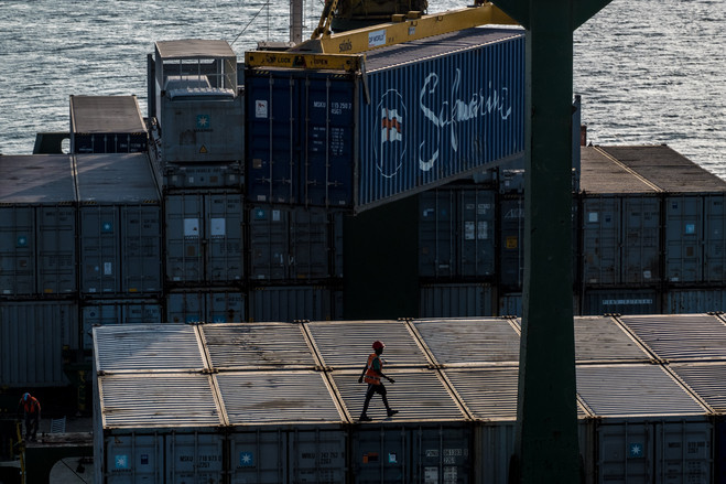 A worker walks over shipping containers on the Sima Pride cargo ship in the port of Berbera.