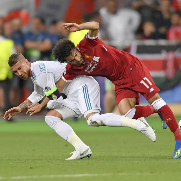 Sergio Ramos, in white, tackles Liverpool's Mohamed Salah in a match that ended in victory for Real Madrid and a shoulder injury for Mr. Salah.