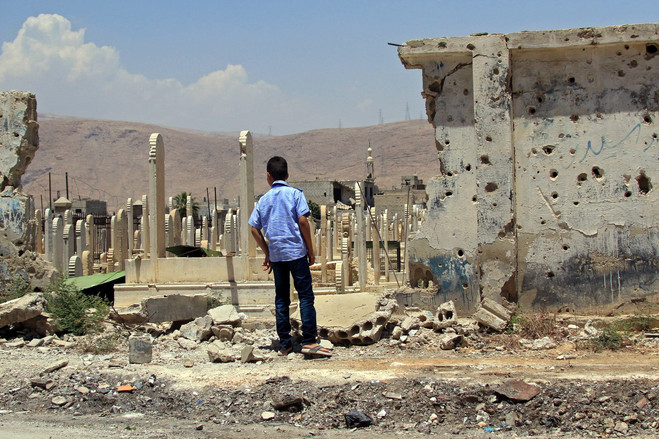 A boy looks at a cemetery amid destroyed houses in Douma, Eastern Ghouta, on June 15.