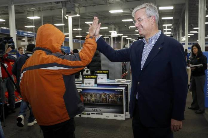 Best Buy CEO Hubert Joly, right, high-fives a customer at one of the electronics retailer's stores in Minnesota in 2015.
