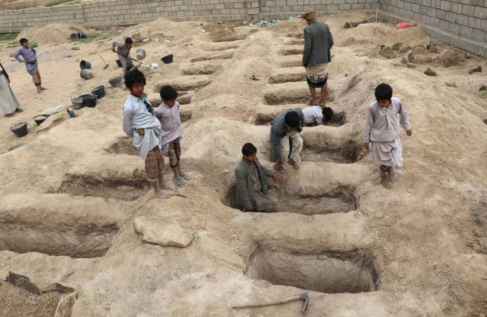 Boys inspected graves prepared for 29 children who died in an airstrike Thursday in northern Yemen.