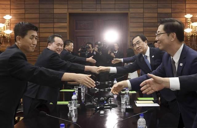 South Korean Unification Minister Cho Myoung-gyon, second from right, shakes hands with his North Korean counterpart Ri Son Gwon, second from left, after their meeting Monday.