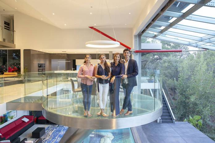 The family stands in a circular glass dining space inspired by the Starship Enterprise.