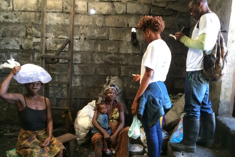Community health worker Mechie Seih gives charcoal seller Mamie Kollie bleach and soap to help her protect herself and her family against Ebola.