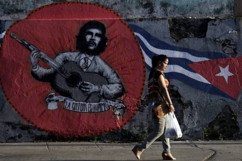 A woman walks past graffiti of Ernesto 'Che' Guevara and a Cuban flag in Havana on Thursday.