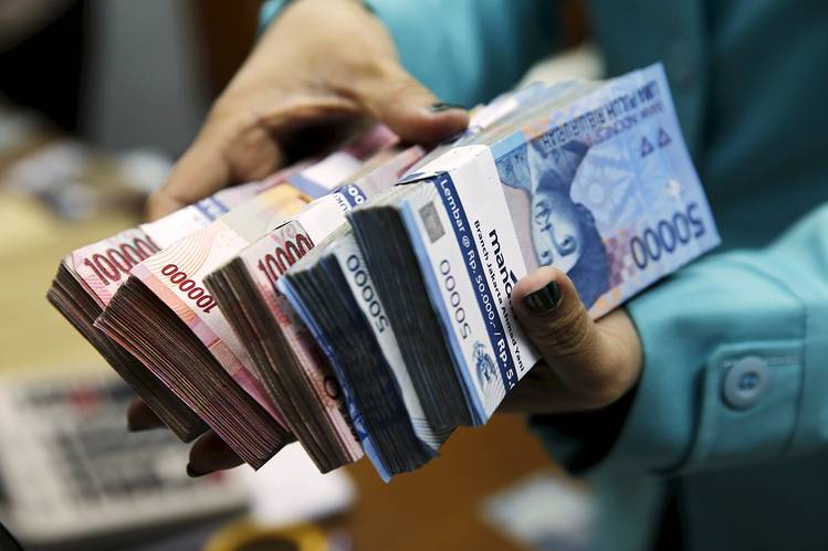 A woman holds Indonesian rupiah notes at a money changer in Jakarta. Indonesia's central bank is pushing through a regulation prohibiting foreign currencies from being used in domestic transactions.