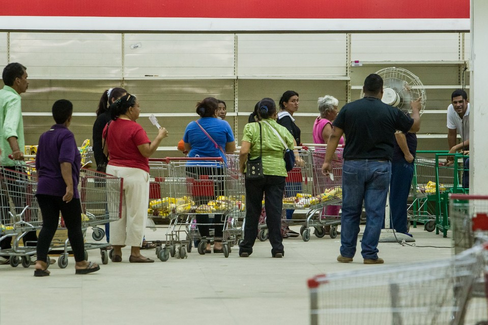 Shoppers wait in a long line inside the state-run Bicentenario supermarket, which sells government subsidized food in Maracaibo.