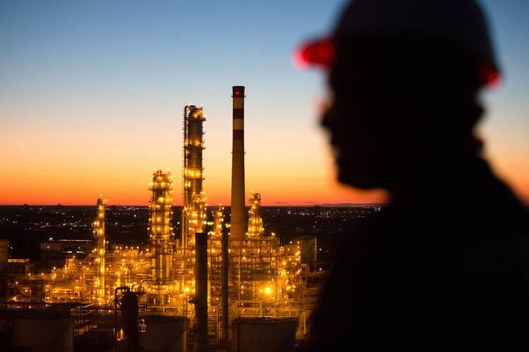 Um trabalhador observa a iluminada refinaria de Atyrau, no Cazaquistão. A taxa de crescimento do país deve cair de 6% antes do colapso dos preços do petróleo para 1,5% neste ano.