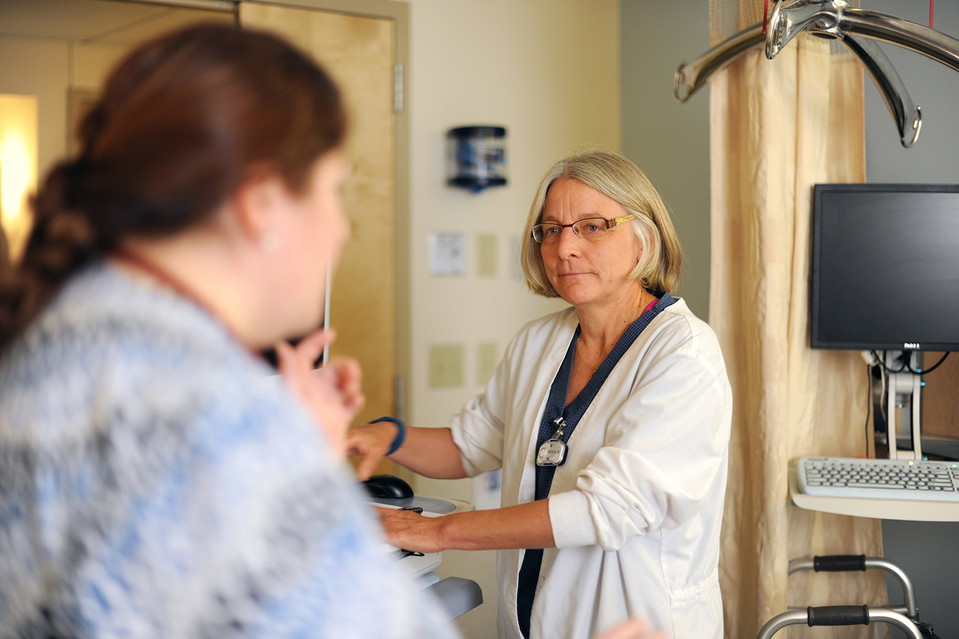 Nurses Corey Bennett, left, and Reenie Mraz-Peterson talk in a patient's room during a shift change at the University of Vermont Medical Center.