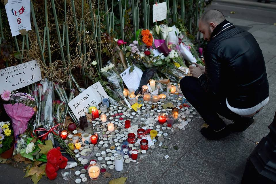 Flowers and tributes on the sidewalk on Sunday near the scene of Friday's attack on the Bataclan concert hall in Paris.