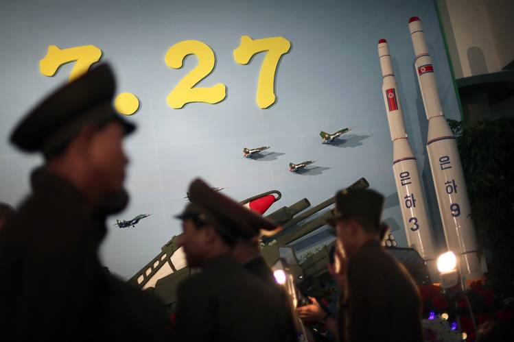 In a file photo from July 2013, North Korean soldiers examined model versions of the Unha-3 rocket, which successfully delivered the country's first satellite into orbit.