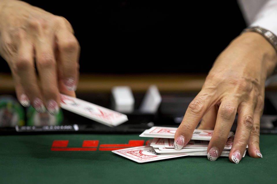 A dealer shuffles a deck of cards  at the World Series of Poker, Friday, May 31, 2013, in Las Vegas.