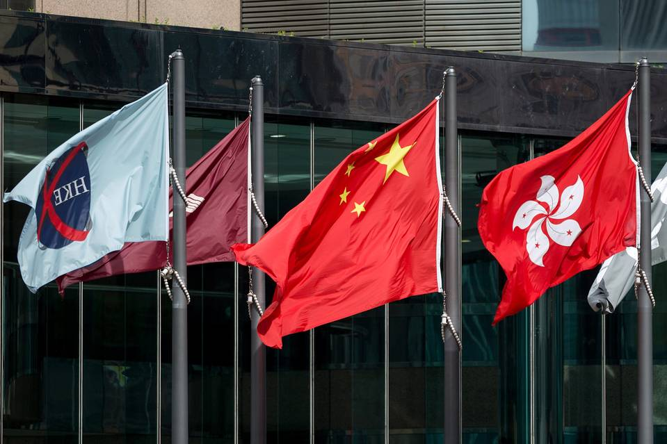 The flags of the Hong Kong stock exchange, China and Hong Kong; a growing number of China's hedge-fund managers are launching new funds in the more stable regulatory environment of Hong Kong.