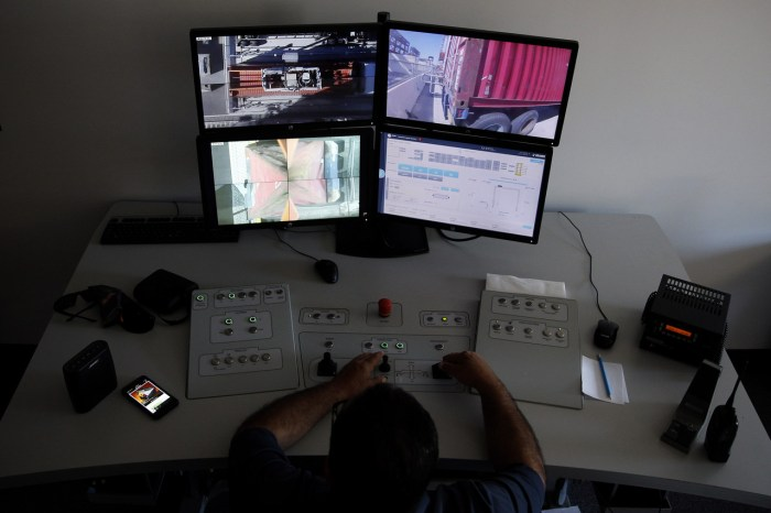 Inside the port terminal office, a worker gently sets containers on truck beds using a joystick and live images of the machinery. On average, he loads more than one truck a minute in this way.