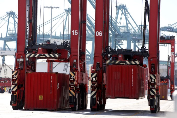 Automated machines pick up and carry cargo containers to stacks at the Port of Los Angeles, guided by a magnetic grid embedded in the pavement.