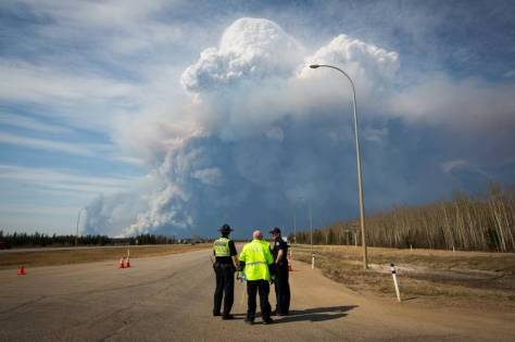 Officers look on near Fort McMurray as smoke from the wildfires billows into the air on Wednesday.