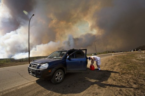 An evacuee puts gas in his car on his way out of Fort McMurray.