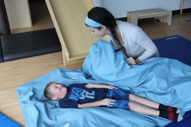 Brody Marsh, who has a sensory-processing condition, works with occupational therapist Beth Johnson at Cincinnati Children's Hospital Medical Center. The exercises give his joints deep-pressure input to compensate for under-responsiveness in the proprioceptive system, causing difficulties with body positioning. Here, the 6-year-old is being squished in a crash mat.