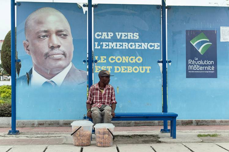 A vendor sat at a bus stand in front of an image of President Joseph Kabila in Kinshasa on Dec. 31.