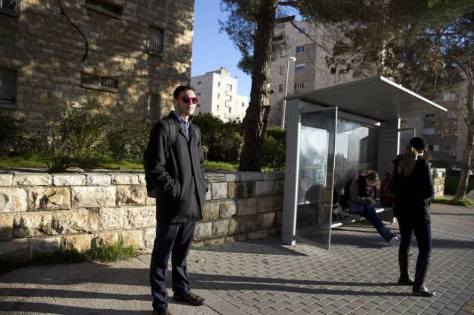 Israelis wait at a bus stop Thursday in French Hill, a largely Jewish neighborhood of East Jerusalem.