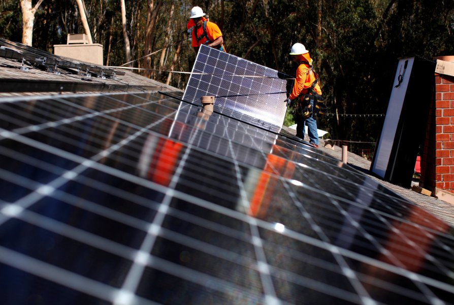 Government Agency Backs Import Protection for U S  Solar Panel     Solar installers from Baker Electric place panels on the roof of a  residential home in Scripps
