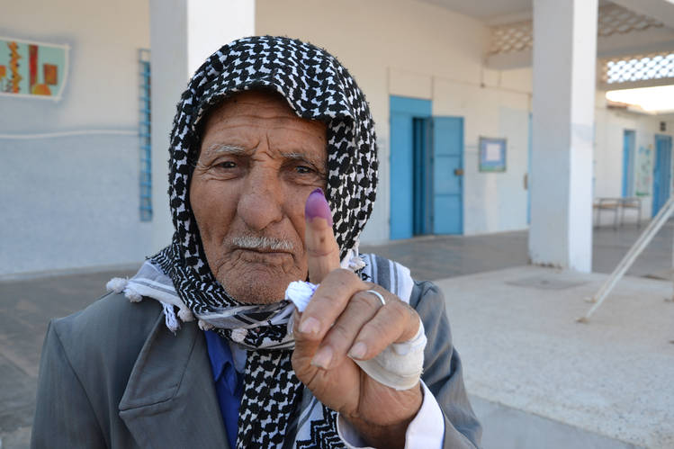 A Tunisian man shows he voted in the country's first presidential elections in 2014.