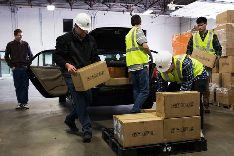 Workers help unload mining rigs dropped off by Michael Poteat (left) at the Bcause facility on Feb. 2. Bcause is aiming to build the largest bitcoin-mining operation in North America.