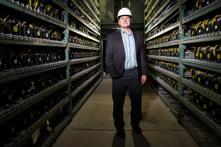 Michael Adolphi, Bcause's chief operating officer, stands between shelves containing hundreds of machines.