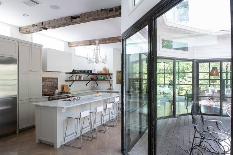 The home's kitchen area uses luxury materials such as Carrera marble and herringbone wood floors.