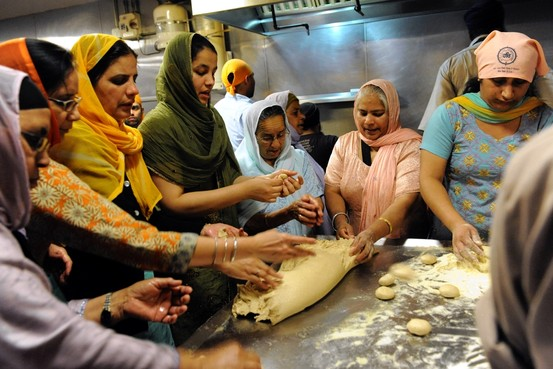 """Volunteers at the Sikh Cultural Society in Richmond Hill, Queens, help prepare a type of flat bread in the kitchen."" (source: wsj.com)"