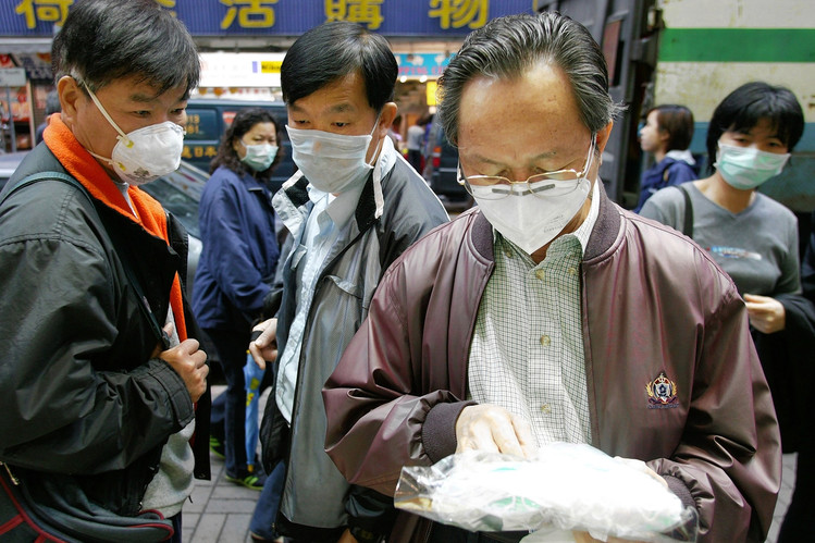 Shoppers in a Hong Kong store check the quality of surgical masks for sale during a deadly outbreak of SARS in 2003.