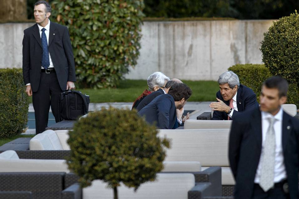 Secretary of State John Kerry, right, talks with members of his delegation in Lausanne on Friday.
