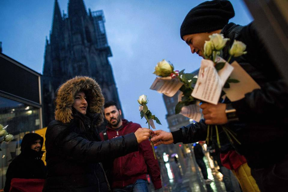 A member of a German-Tunisian association handed out flowers Thursday near the site of scores of holiday assaults in Cologne, Germany.