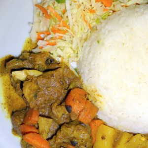 curry goat with white rice and Jamaican cabbage slaw