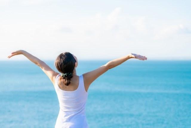海岸で女性が気持ち良く背伸びをしている写真