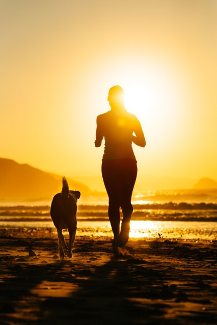 Woman and dog running towards the sun