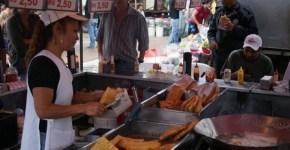 Pastelaria de feira usando tacho para fritar pastel