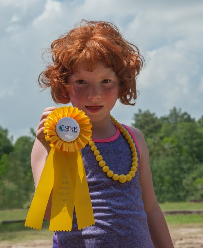 Emileigh Marsh shows off one of the ribbons won at the All SIRE Horse Show in May 2014.  Photo by Jaana Eleftheriou