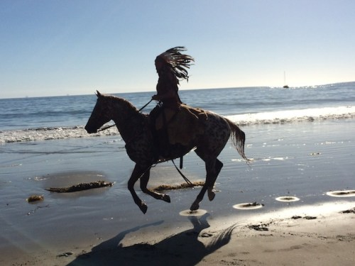 Kerstie gallops down the beach during a photo shoot.