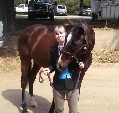Lina and Ruby posing with a medal and ribbon they earned at the 2014 Special Olympics North Carolina Equestrian Tournament. (Photo by Tracy Franklin)