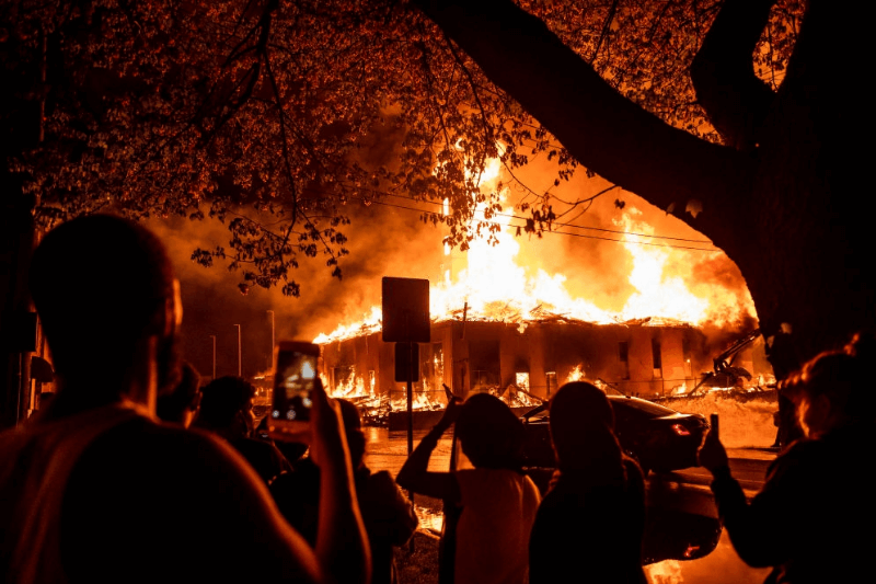 "MINNEAPOLIS, MN - MAY 27: People look on as a construction site burns in a large fire near the Third Police Precinct on May 27, 2020 in Minneapolis, Minnesota. A number of businesses and homes were damaged as the area has become the site of an ongoing protest after the police killing of George Floyd. Four Minneapolis police officers have been fired after a video taken by a bystander was posted on social media showing Floyd's neck being pinned to the ground by an officer as he repeatedly said, ""I can't breathe"". Floyd was later pronounced dead while in police custody after being transported to Hennepin County Medical Center."