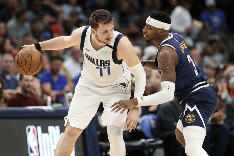 Mar 11, 2020; Dallas, Texas, USA; Dallas Mavericks guard Luka Doncic (77) dribbles as Denver Nuggets forward Torrey Craig (3) defends during the second half at American Airlines Center.